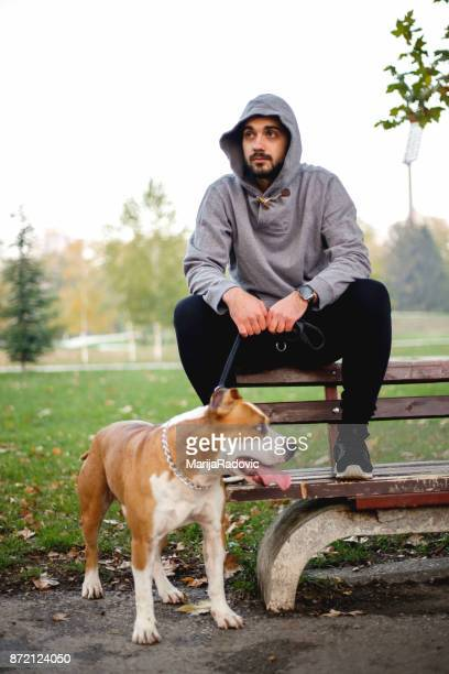 Young man exercising in a park with his dog