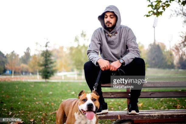 Jonge man uitoefenen in een park met zijn hond