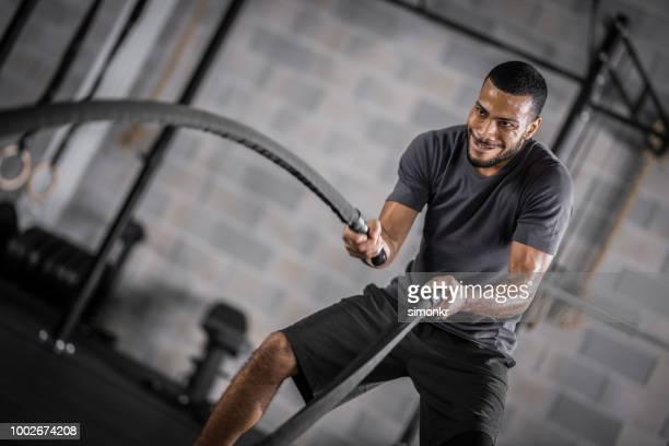 young man exercising in gym - pantaloncini grigi foto e immagini stock