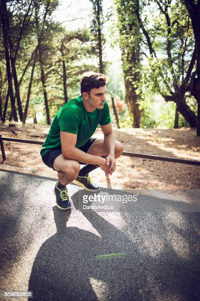 young man exercising in nature - hand on knee stock pictures, royalty-free photos & images