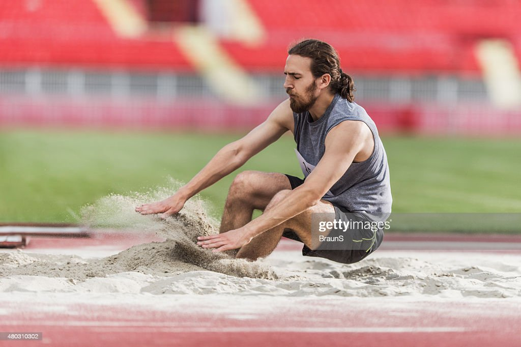 Young man exercising long jumps and landing in a sand. : Stock Photo