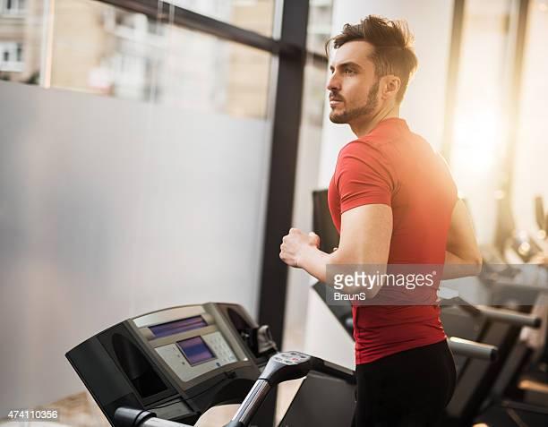 Young man ejercítes'en la máquina trotadora en un club de salud.
