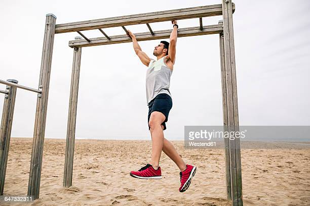 Young man exercising on monkey bars on the beach