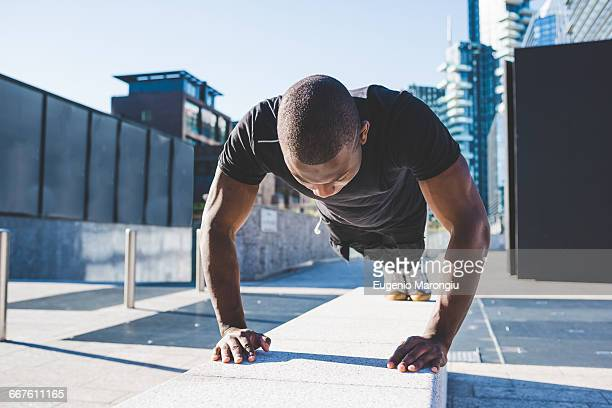 young man exercising outdoors, doing push-ups - push ups stock pictures, royalty-free photos & images