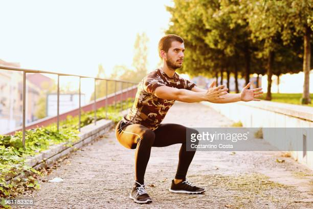 young man exercising outdoors, doing squats - hurken stockfoto's en -beelden