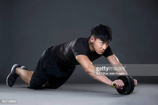 Young man exercising with Ab wheel