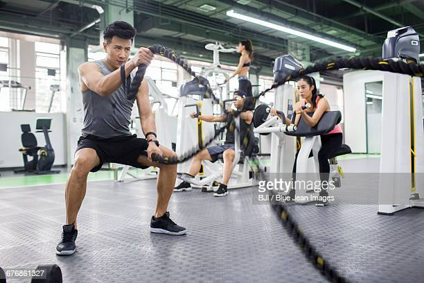 young man exercising with battling rope at gym - circuit training stock photos and pictures
