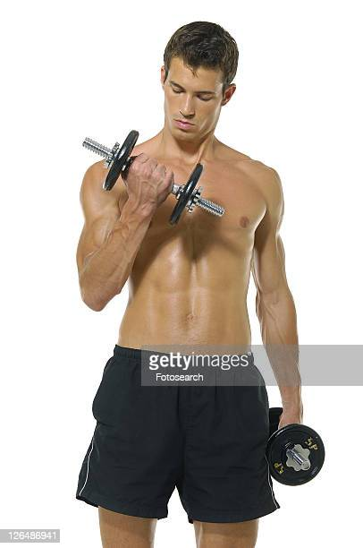 Young man exercising with hand weights