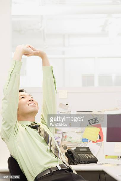 Young man exercising with stretch in office cubicle