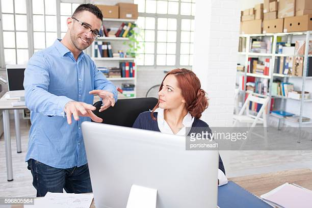 Young man explaining his ideas to secretary at the office