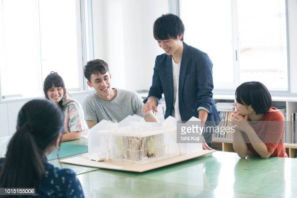 A young man explaining the model of architecture