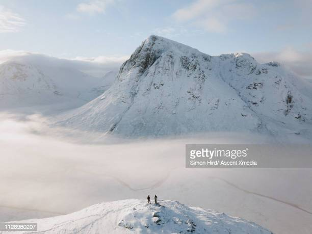 young man explores snowy ridge above mountain peak - scotland stock pictures, royalty-free photos & images
