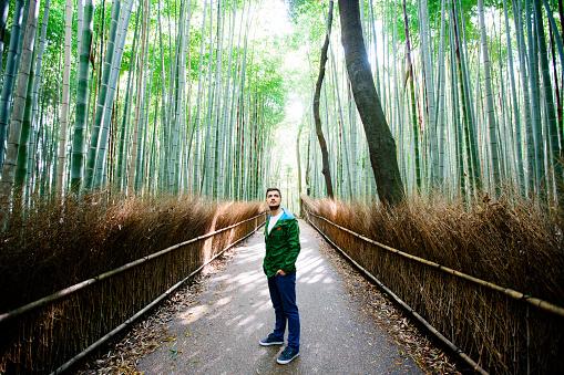 Young man exploring Arashiyama bamboo grove in Kyoto, Japan - gettyimageskorea