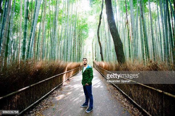 Young man exploring Arashiyama bamboo grove in Kyoto, Japan