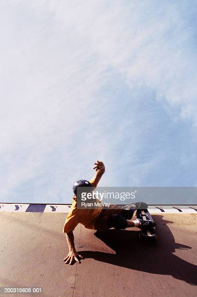 Young man falling off skateboard