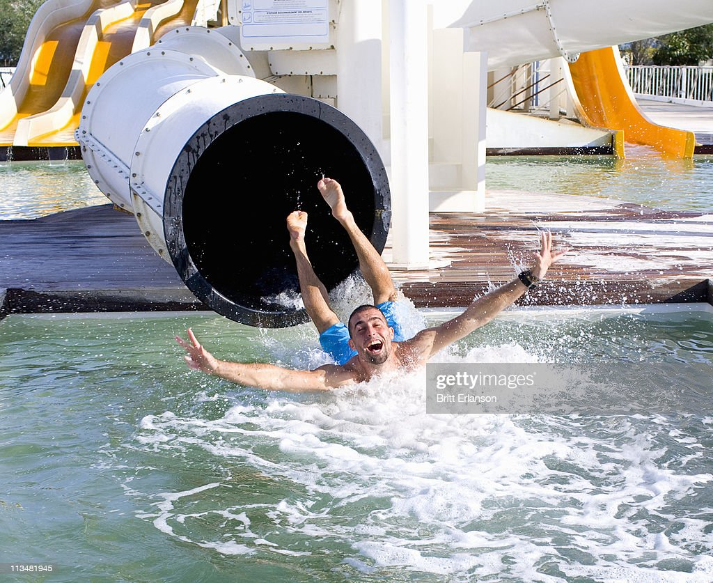 Young man falls into pool from slide : Stock Photo
