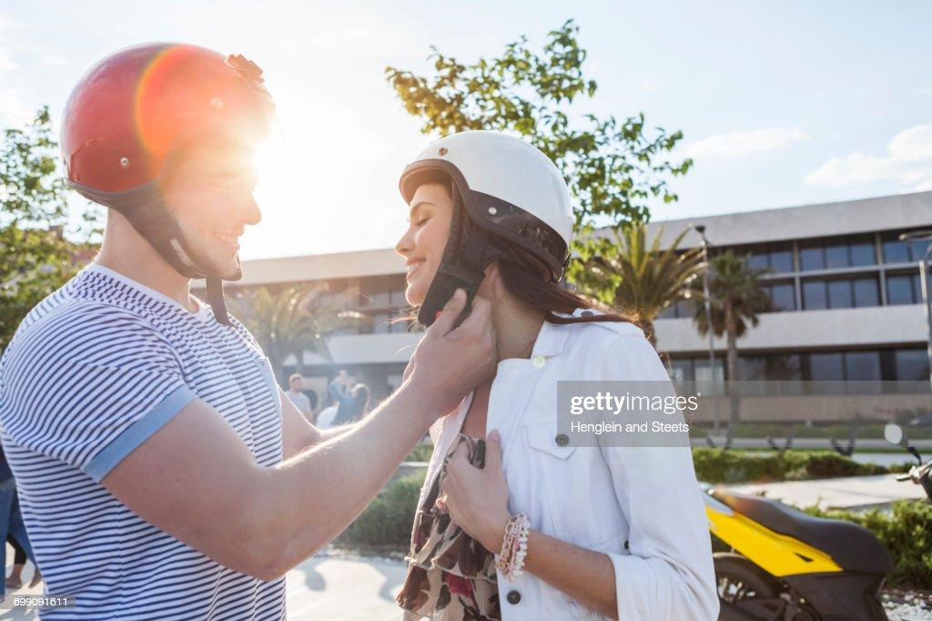 Young man fastening girlfriends crash helmet, Split, Dalmatia, Croatia : Stock Photo