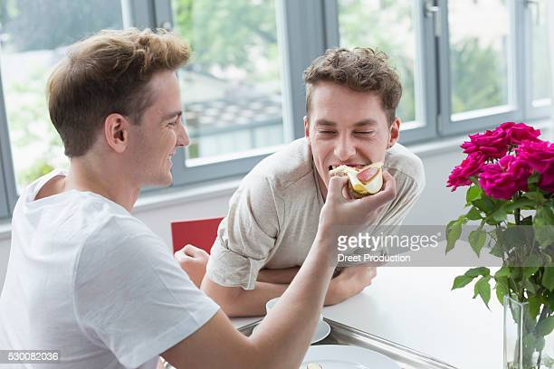 Young man feeding bread to another man, smiling