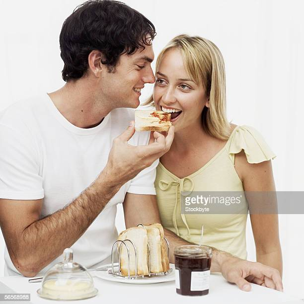 young man feeding toast to a young woman