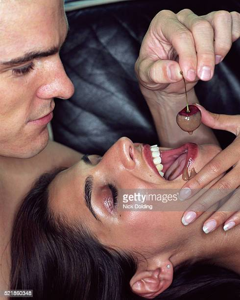 young man feeding woman with cherry - couple chocolate stock pictures, royalty-free photos & images