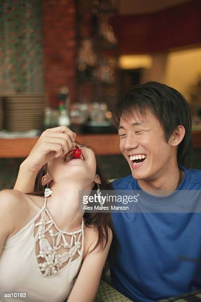 Young man feeding young woman a cherry