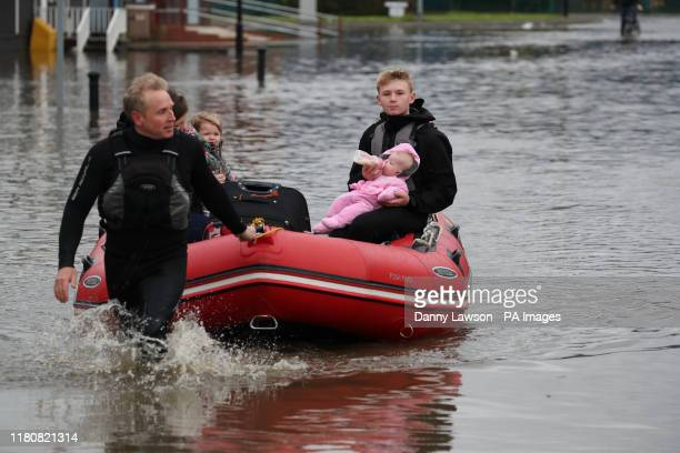 Young man feeds a child a bottle of milk as his father pulls an inflatable boat they have been using to rescue residents trapped by floodwater in...