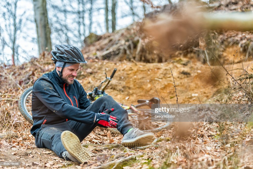 Young man fell off mountain bike : Stock Photo