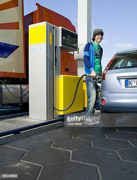 young man filing car at petrol station
