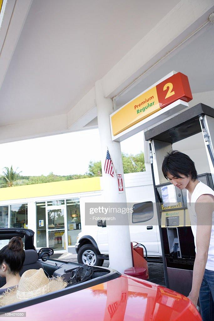 Young man filling car in gas station, Saipan, USA : Stock Photo
