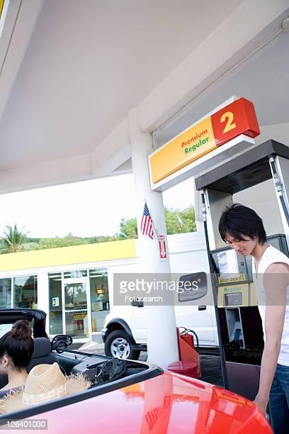 Young man filling car in gas station, Saipan, USA