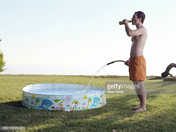 Young man filling plastic pool with water from hose