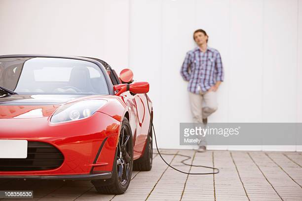young man filling up his electric car - elektroauto stock-fotos und bilder