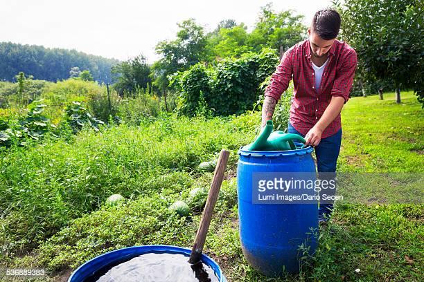 Young man filling watering can at barrel