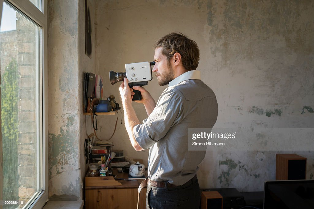 Young man filming with a super 8 movie camera : Stock Photo