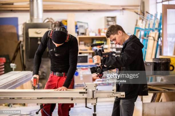 young man films carpenter in workshop - gifted movie stock pictures, royalty-free photos & images