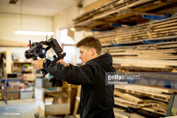 young man films in carpentry shop - gifted movie stock pictures, royalty-free photos & images