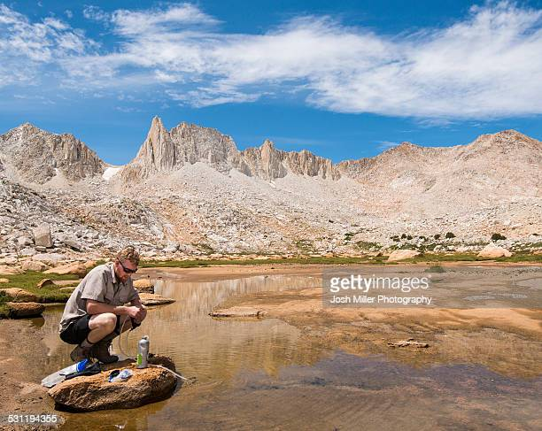 Young Man filtering water in the Granite Park of the High Sierra
