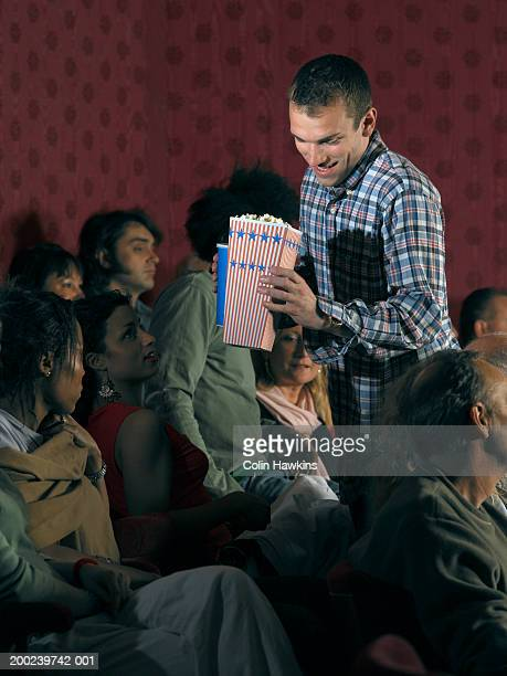 young man finding seat in crowded theatre, holding popcorn - colin hawkins stock pictures, royalty-free photos & images
