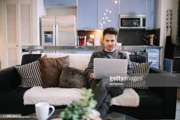 young man finishing work on on the sofa in the living room of an los angeles loft apartment - surfing the net stock pictures, royalty-free photos & images