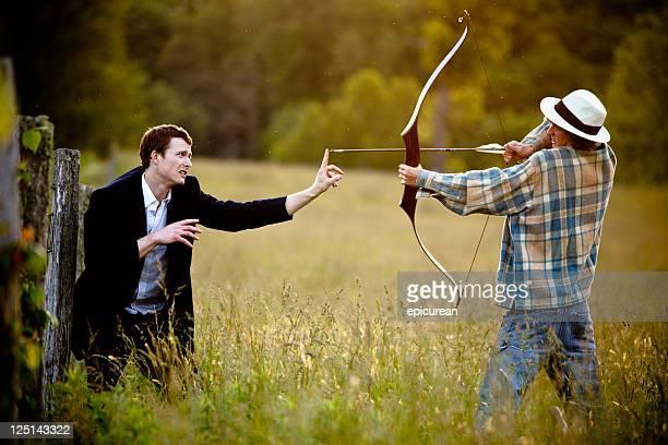 Joven de disparo arco y flecha hacia un hombre de negocios