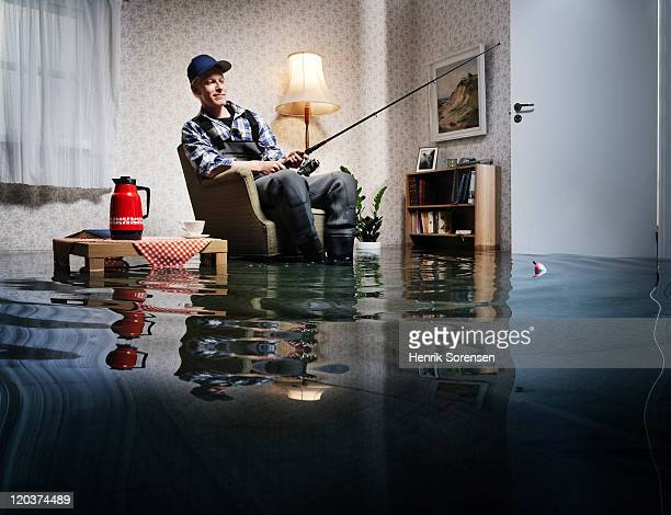 young man fishing in flooded room - konzepte und themen stock-fotos und bilder