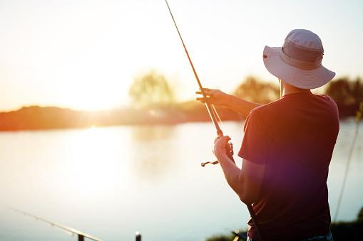 Young man fishing on a lake at sunset and enjoying hobby 869710006