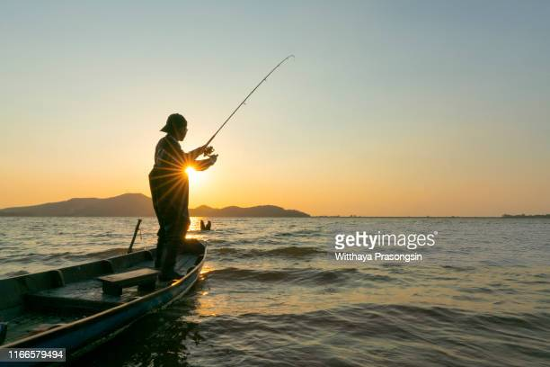 young man fishing on a lake from the boat at sunset - 淡水釣り ストックフォトと画像