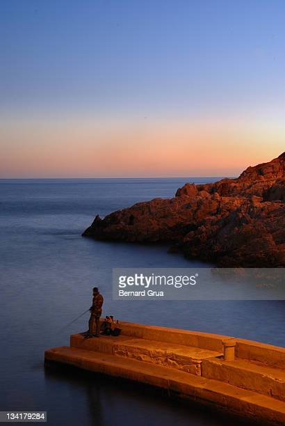 young man fishing on small pier at sunset - bernard grua photos et images de collection