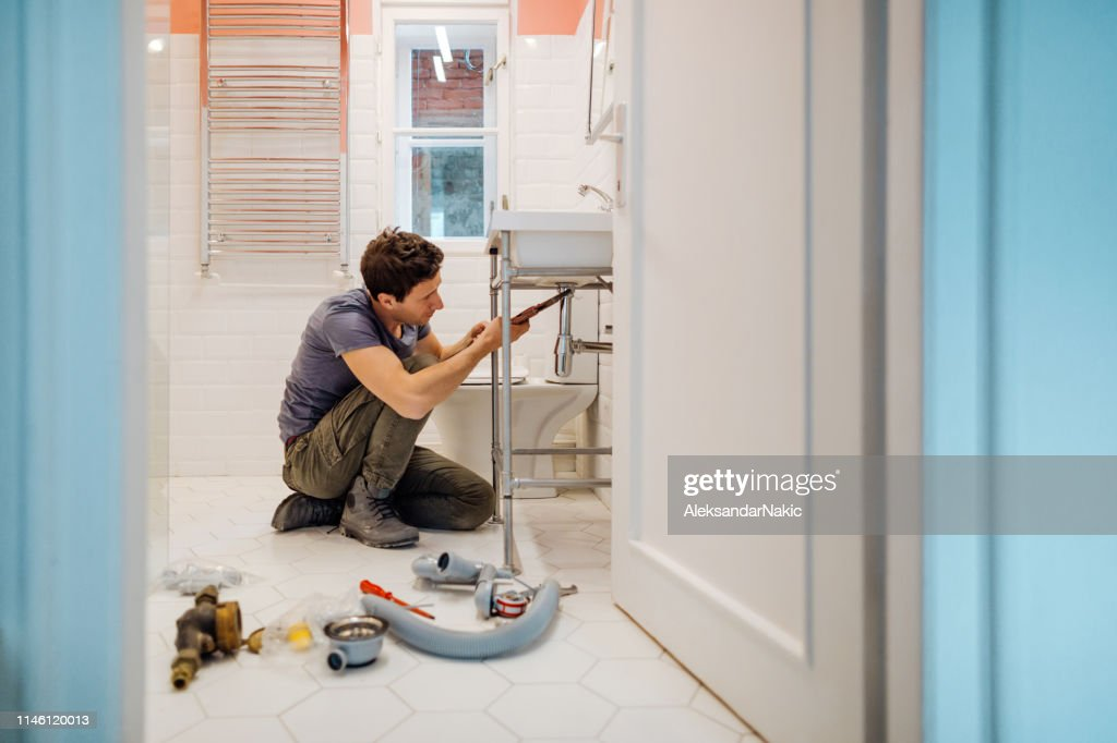 Young man fixing a leak under the bathroom sink : Stock Photo