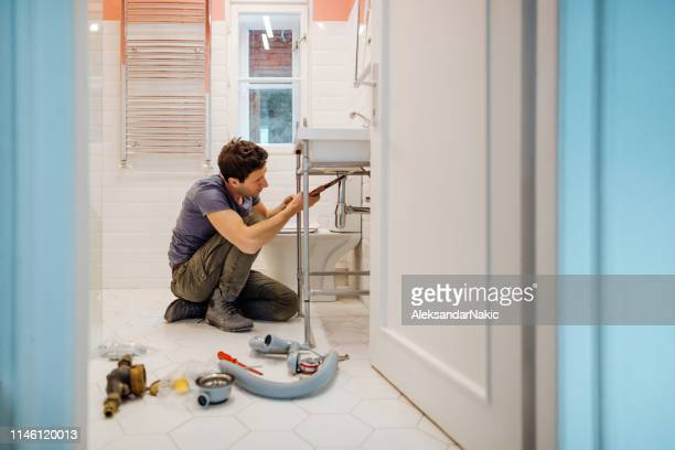 young man fixing a leak under the bathroom sink - lavandino foto e immagini stock