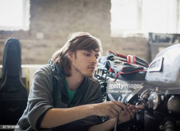 young man fixing motorcycle indoors - vintage auto repair stock pictures, royalty-free photos & images