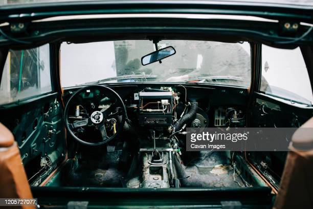 a young man fixing up an old classic car. - weathered stock pictures, royalty-free photos & images