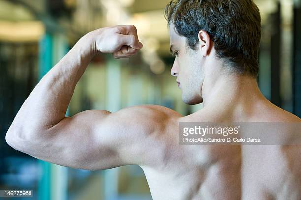 Young man flexing bicep muscles