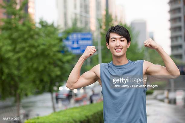 Young man flexing his muscles